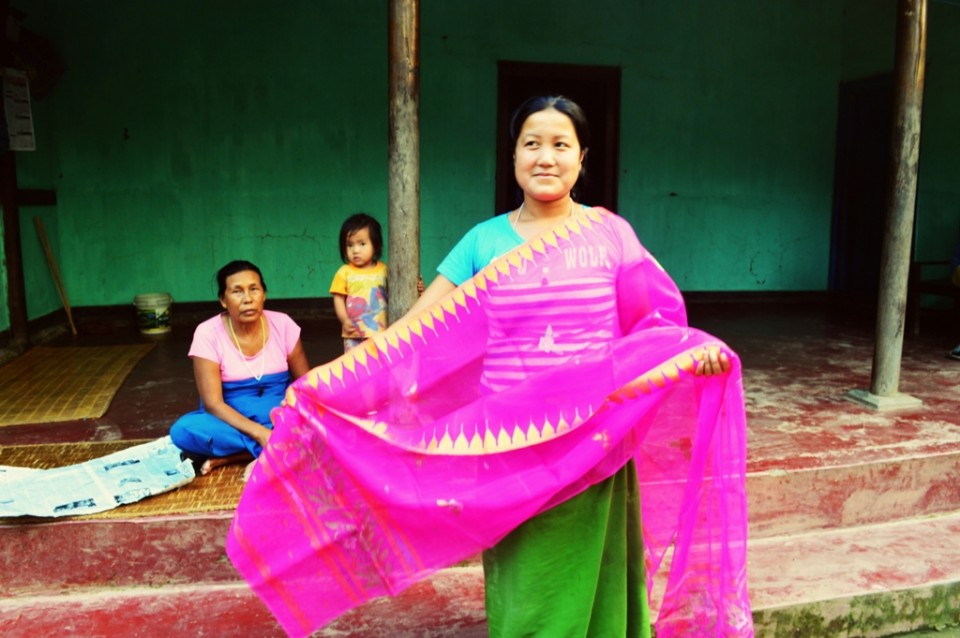 A weaver displays a finished shawl